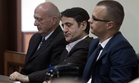 Kosovo Albanian doctor Lutfi Dervishi, centre, flanked by his legal team, awaits the judge's verdict in a court in Pristina. Photograph: Visar Kryeziu/AP