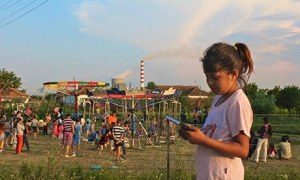 Children play as Kosovo B power plant in Plemetina belches toxic fumes behind them. Photograph: Harriet Salem