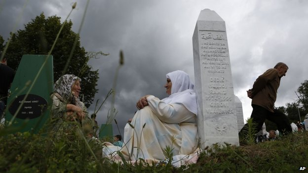 Bosnian Muslim women rest near a gravestone during a funeral in Srebrenica, Bosnia on 11 July  2014. The Muslim-majority town was a UN-protected area besieged by Serb forces throughout the war