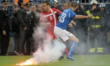 Dragan Mrdja and Leonardo Bonucci are nearly hit by a flare. Photograph: Giuseppe Cacace/AFP/Getty Images