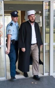 A policeman escorts Sefqet Krasniqi, imam of Pristina's Grand Mosque. [AFP]