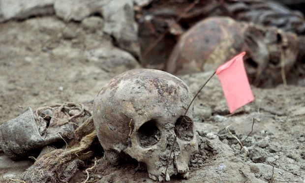 Bosnian forensic experts uncover and catalogue bodily remains found in a mass grave in the eastern village of Kamenica, near the town of Zvornik, close to the border with Serbia on 25 July 2002. Photograph: Reuters/Corbis