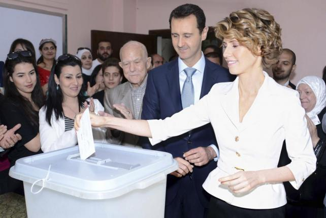 Syria's President Bashar al-Assad and his wife Asma (R) cast their votes in the country's presidential elections at a polling station in Damascus June 3, 2014, in this handout released by Syria's national news agency SANA. REUTERS/SANA/Handout via Reuters